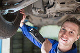 Portrait of mechanic examining tire