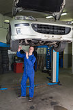 Mechanic working under raised car in workshop