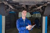 Mechanic preparing checklist under car