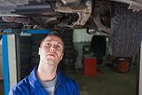 Repairman standing under car