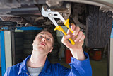 Mechanic repairing car with adjustable pliers