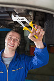 Mechanic repairing car with pliers