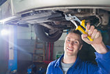 Happy mechanic repairing car with pliers