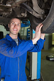 Happy mechanic examining car tire