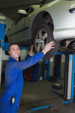 Car on hydraulic lift as mechanic examining tire