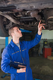 Auto mechanic with clipboard under car