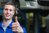 Smart car mechanic gesturing thumbs up
