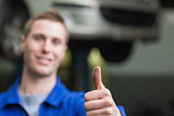 Auto mechanic gesturing thumbs up