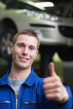 Handsome car mechanic gesturing thumbs up