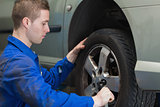 Male mechanic changing car wheel