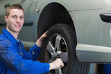 Happy mechanic changing car tyre