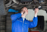 Mechanic on call while examining car