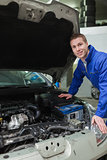 Happy mechanic repairing car engine