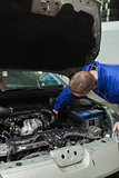 Mechanic working under bonnet of car