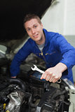 Mechanic with spanner repairing car