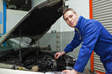 Confident mechanic checking car engine oil