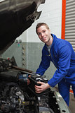 Happy mechanic with battery by car