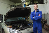 Confident auto mechanic by car