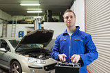 Mechanic carrying car battery