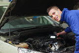 Confident repairman examining car engine
