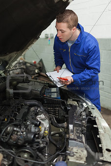 Car mechanic preparing checklist