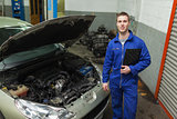 Mechanic standing by car with open hood