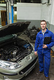 Confident mechanic standing by car with open hood