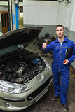 Mechanic by car showing thumbs up sign