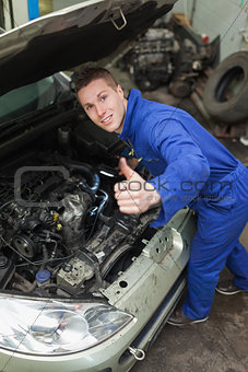 Auto mechanic showing thumbs up sign