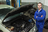 Confident repairman by car with open hood