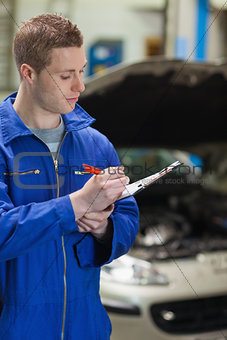 Auto mechanic writing on clipboard