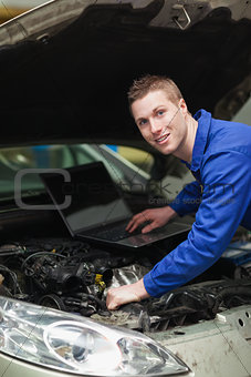 Car mechanic with laptop checking engine