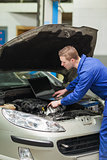 Auto mechanic with laptop repairing car