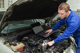 Mechanic with laptop repairing car