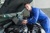 Male auto mechanic using laptop
