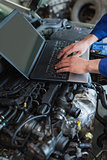 Car mechanic using laptop