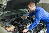 Mechanic with digital tablet repairing car engine