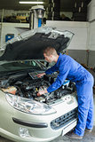 Male mechanic analyzing car engine