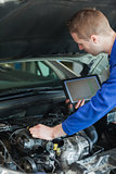 Repairman with tablet pc repairing car engine