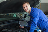Male mechanic holding tablet pc