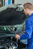 Mechanic with tablet pc examining car engine
