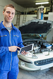 Happy mechanic using tablet computer