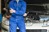 Mechanic leaning on car with open hood