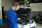 Male mechanic using laptop