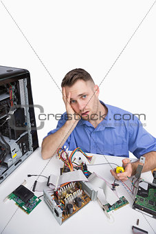 Portrait of tired computer engineer with cpu parts