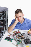 Portrait of young tired computer engineer with cpu parts