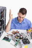 Confused young computer engineer fixing computer parts