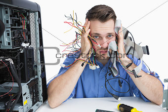 Portrait of tired it professional with cables in hands