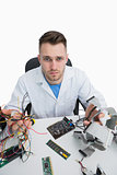 Portrait of confused computer engineer with cpu parts