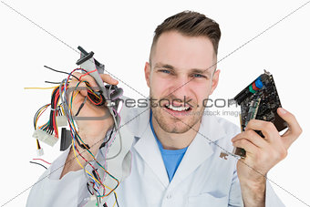 Portrait of young it professional yelling with cpu parts in hands